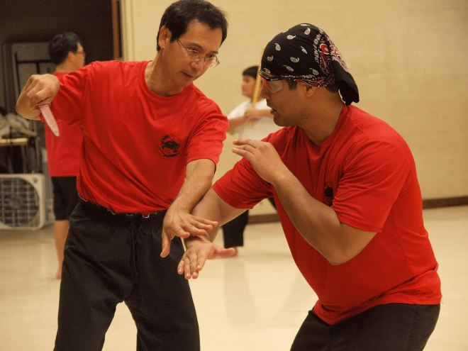 Maestros Donald Mendoza (right) and C.J. Tobosa (left) of Tobosa School of Kali Escrima practice sparring with a dagger at Halawa Gym.
