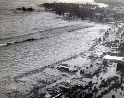 One of the newly acquired aerial images from the 1946 tsunami. An earthquake in the Aleutian Islands generated a tsunami that struck the Hawaiian Islands at approximately 7 a.m., about the time that people were having breakfast or getting ready for work and school. There was no warning system in 1946; therefore, people were taken by surprise. Witnesses stated that before the third wave came into Hilo Harbor, the water receded all the way out to Hilo's breakwater. Photo Courtesy of the PTA Archives: James Kerschner's U.S. Naval Air Station Collection.
